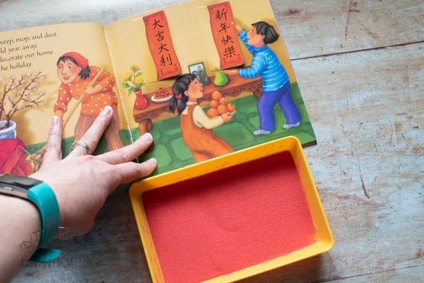 finding chinese symbols in the book dragon dance and using making them in the sand of a simple Montessori sand tray