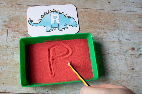 writing with a pencil in a sand tray