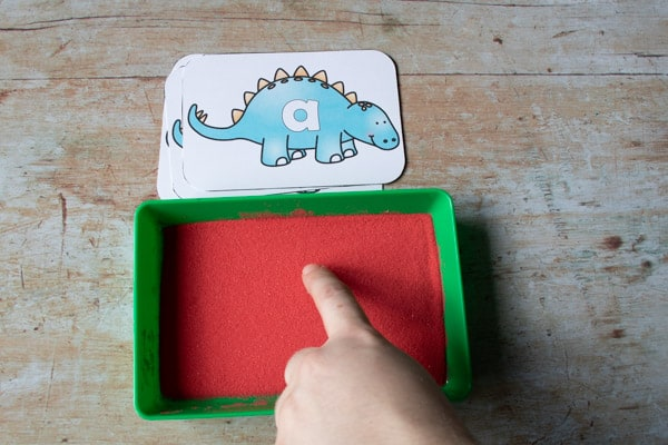 using a finger to make letters in a sand tray