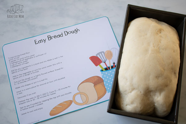 bread dough rising with a recipe card for kids to use beside it on a marble counter top