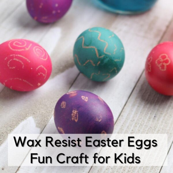 coloured eggs for an easter egg hunt with wax designs on them on a wooden table text reads Wax Resist Easter Eggs Fun Craft for Kids