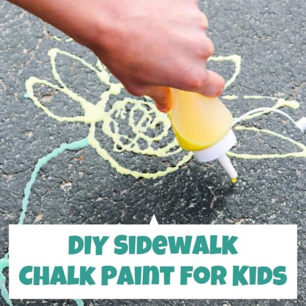 DIY Sidewalk chalk paint being used to draw a sunflower on the drive