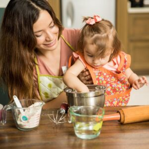 Mum and toddler cooking together at the table one of the top tips for cooking with toddlers on Rainy Day Mum