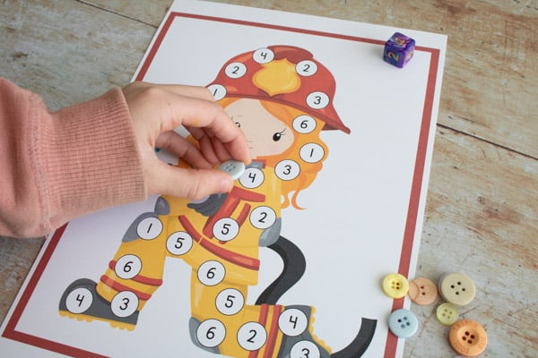 playing a diy maths game using dice and buttons for counters
