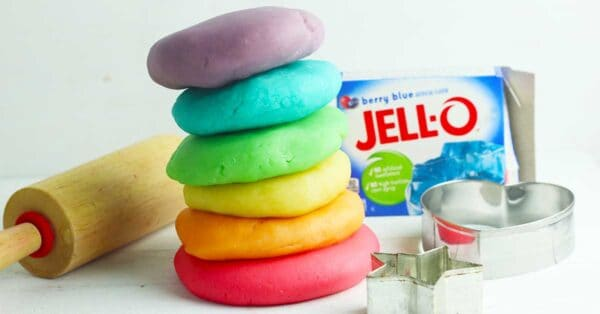 a stack of rainbow coloured playdough balls on a white white table with a wooden rolling pin, metal cookie cutters and a packet of berry blue jell-o behind
