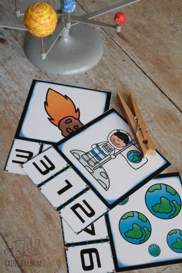 Count and clip cards with a space theme set up for a toddler to practice counting and number recognitioion