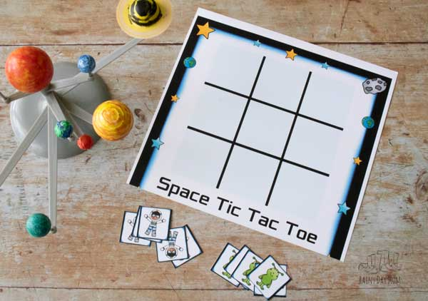 space themed tic tac toe game with a set of printable alien and astronaut counters next to a homemade solar system from a kit on a wooden background