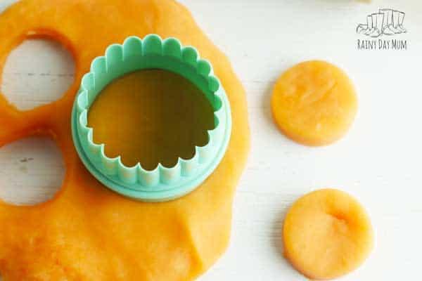 orange playdough with a circle cutter
