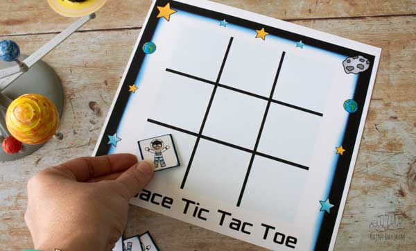 playing space tic tac toe with kids taking turns to lay the pieces on the printed board game