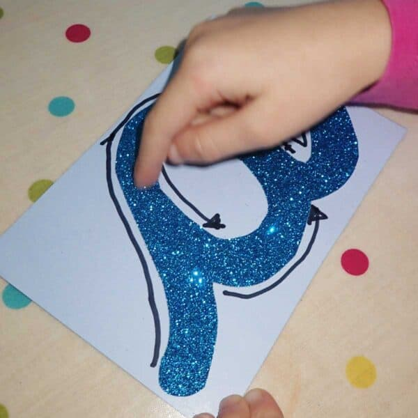 child tracing over a DIY sensory letter card