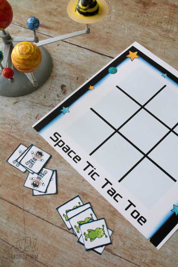space themed tic tac toe game printed on card on a wooden background with a solar system model beside it