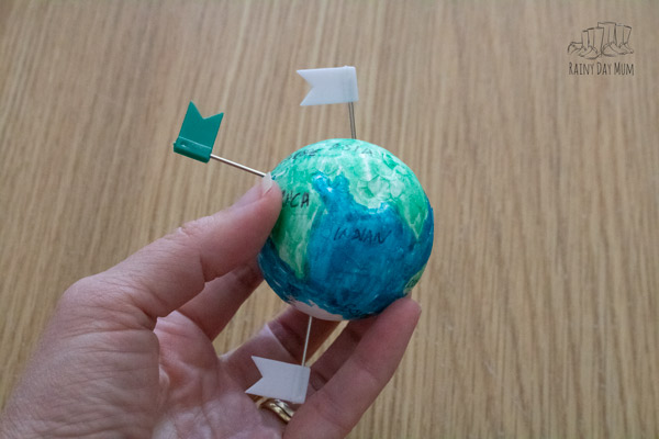poles and the UK marked on a handmade mini globe for Geography with flag push pins