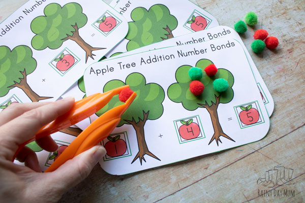 placing a pompom apple on the tree to complete the number bond sum