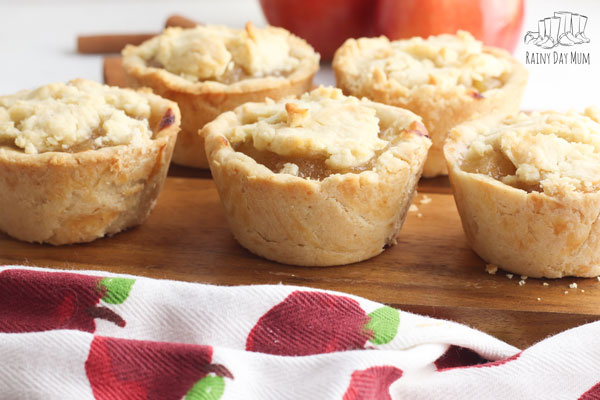 5 homemade apple pies cooked by a kid on a wooden board with an apple fabric in front