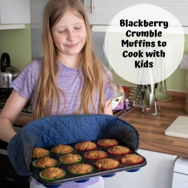 girl holding a muffin tray of blackberry crumble muffins
