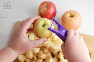 child peeling apples over a wooden chopping board