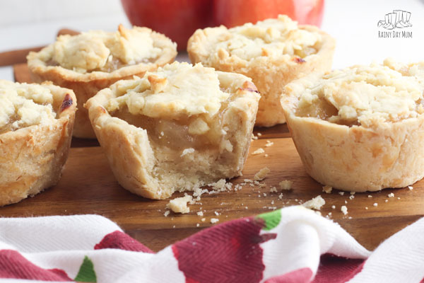 collection of apple pies on a wooden chopping board with an apple cloth in front, one of the pies is half eaten showing the delicious apple pie filling