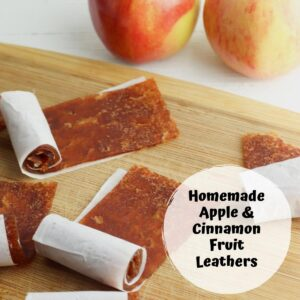 apple and cinnamon fruit leathers on a wooden chopping boards with apples in the background
