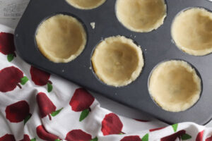 no-roll pastry crust in a muffin tin ready to be filled with apples