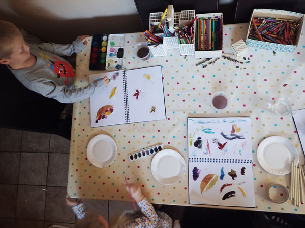 kids at the kitchen table doing autumn art as part of homeschooling