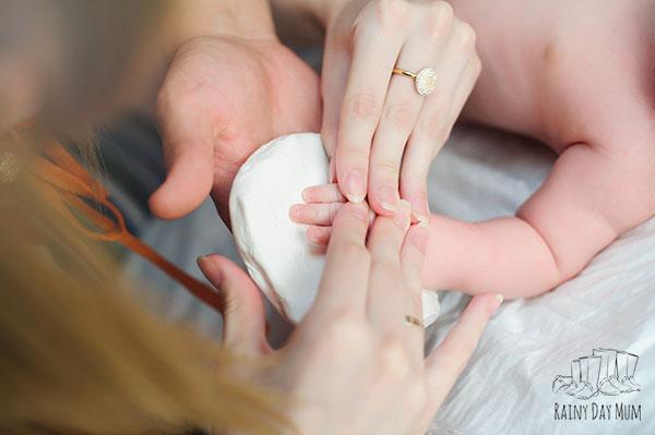 mother capturing her babies handprint in salt dough