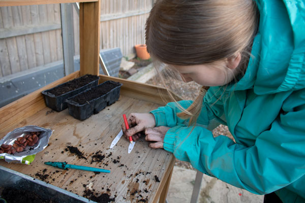 girl writing on plant labels in a green house