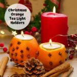 2 orange pomander tea light holders with a candle, pine cones and cinnamon sticks made by kids as an easy Christmas Craft