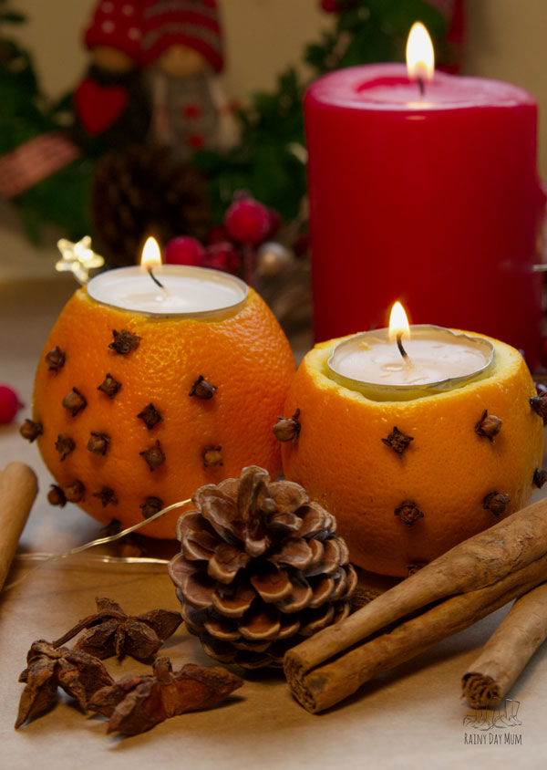 orange tea light holders with cloves in for natural scent and beautiful light at Christmas a simple DIY for you to make