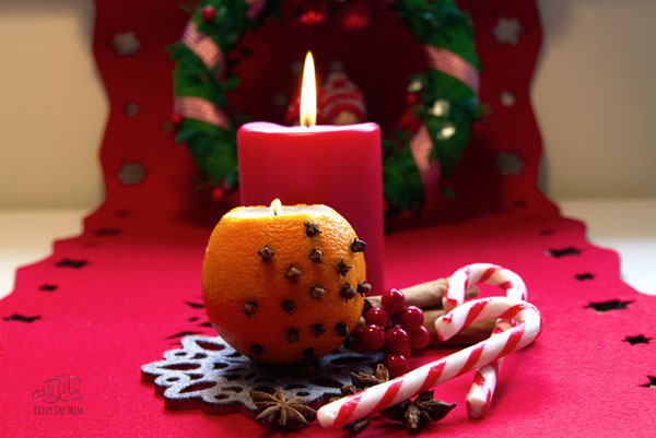 orange tea light holder on a red runner with candy canes