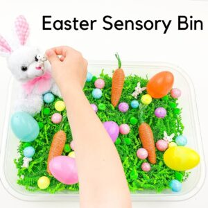 child playing in an Easter Sensory Tub. The sensory tub has green easter grass plus Easter themed objects text on the top reads Easter Sensory Bin