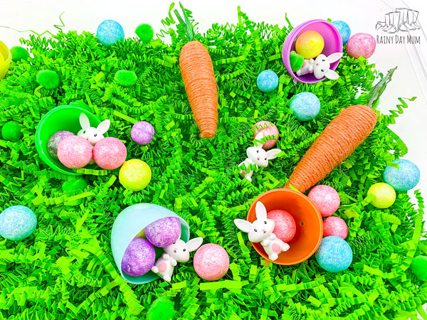 easter sensory bin with green easter grass, jute wrapped carrots, glitter balls, plastic easter eggs split apart and mini bunnies ready for counting, pouring, playing and learning fun