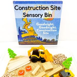 goodnight goodnight construction site board book placed above a simple construction themed sensory tub set up ready for a child to play. The sensory tub is filled with trucks, blocks, cones and trees on a bed of rice and pinto beans ready for play.