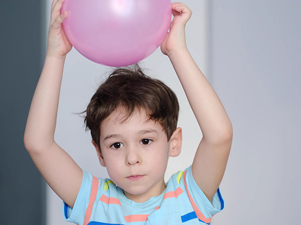 little boy rubbing a balloon on his head  to create static electricity with his hair