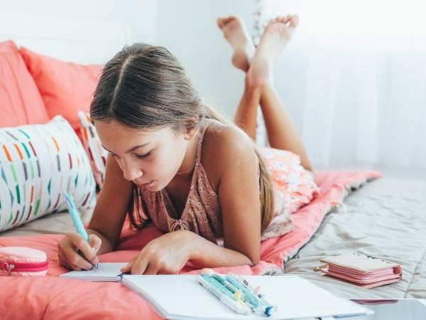 young girl laying on her bed journaling in a notebook