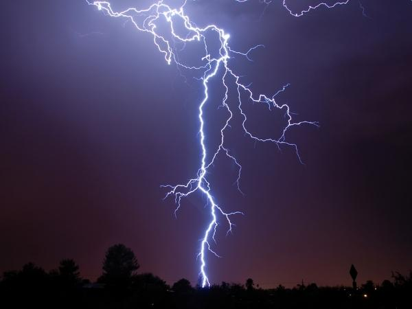photograph of a lightning strike against a dark purple sky with a silhouette of trees and buildings at the bottom