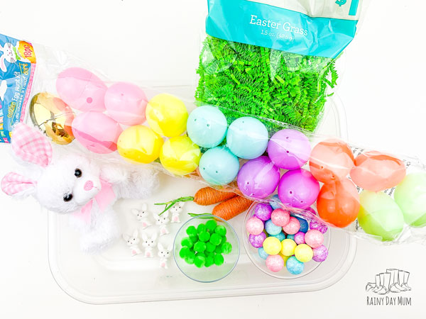 materials for setting up an Easter Sensory Tub, easter grass, plus bunny, plastic easter eggs, green pom poms, glitter balls, fake carrots and mini bunnies