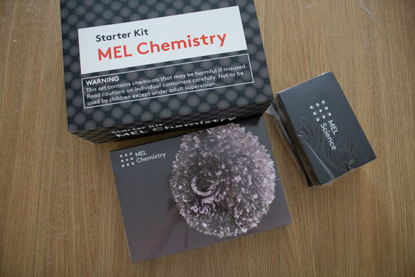Mel Chemistry Starter Kit box, VR headset and the first experiment box as part of the subscription on a wooden table
