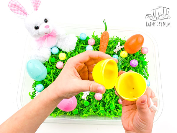 hands holding a plastic easter egg with the ears of a mini bunny just visible about to hide it inside behind the hands a simple Easter sensory tub set up for her child to play