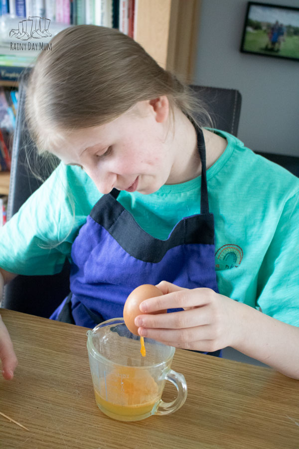 girl saving the egg yolk from an egg that she's going to decorate for Easter after having blown it