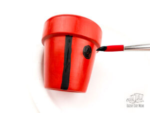 adding the division of the wings of a ladybird and spots to a painted clay pot for a ladybug planter kids can make