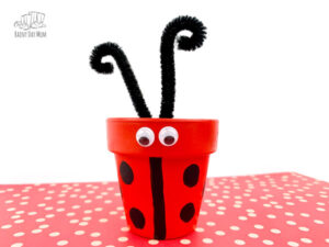 clay pot ladybug craft finished with pipe cleaner antenae on a red spotted paper against a white background
