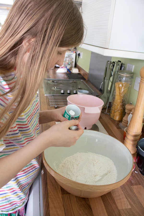 girl measuring out ingredients for a recipe in the home kitchen