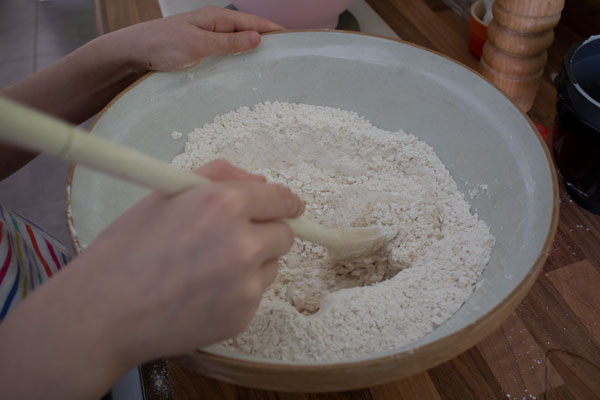 mixing the water into dry ingredients for Viking bread in a bowl with a wooden spoon