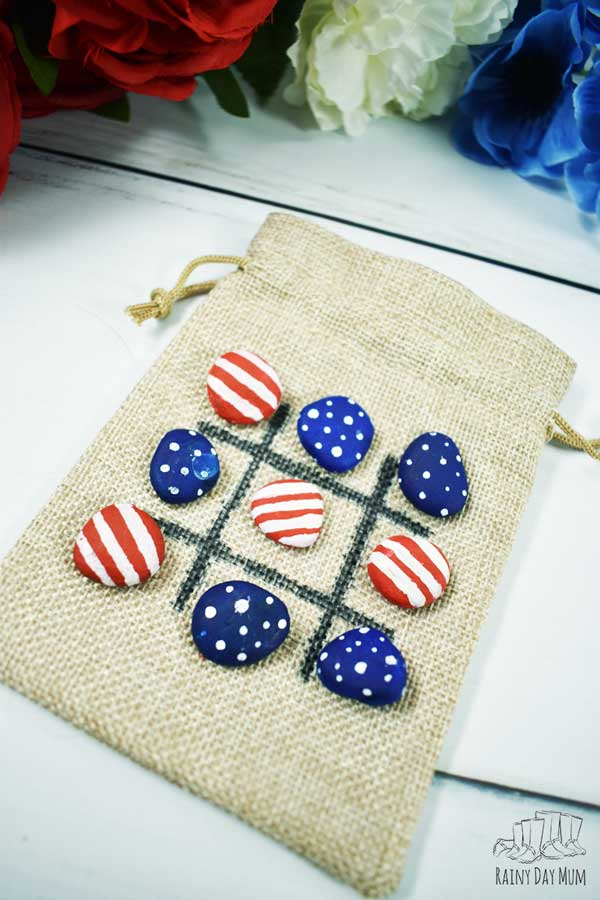 tic tac toe stars and stripes painted rocks on a board on a burlap bag all set up with neither side winning. The bag is placed on a white wooden table with some red, white and blue flowers behind