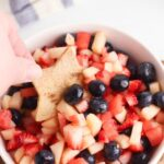 a hand dipping a homemade star shaped cinnamon coated tortilla chip into a bowl with a red white and blue fruit salsa in , you can see blueberries strawberries, watermelon and apple slices in the bowl