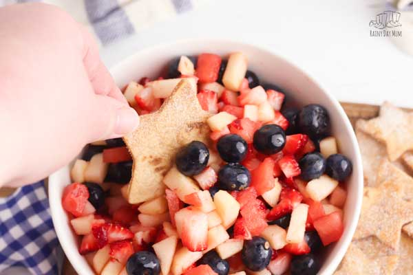 a hand dipping a star shapped cinnamon coated tortilla chip into a red white and blue fruit salad