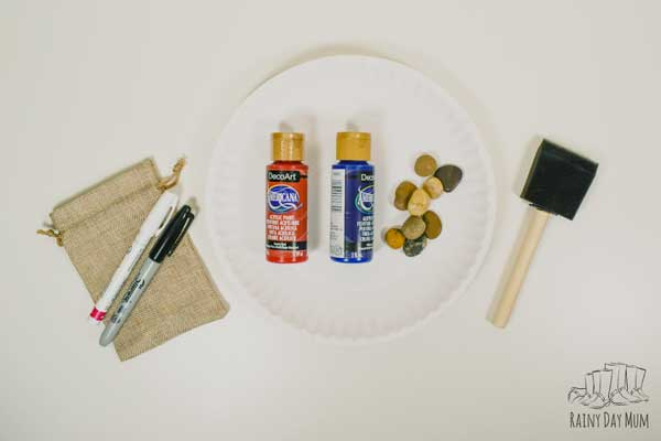 materials for making a set of 4th of July tic tac toe painted rocks, burlap bag, markers, paints, paper plate, pebbles and foam brush