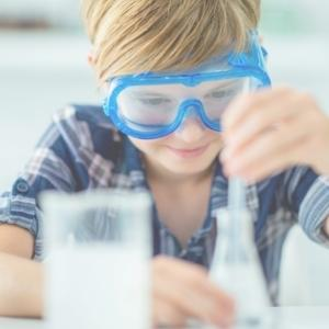 boy doing a chemistry experiment with a pipette and conical flask transferring to a beaker