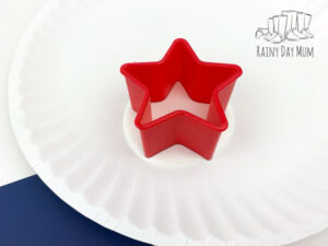 a red star cookie cutter in white paint on a washable white paint