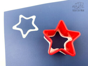 2 printed cookie cutter star shapes on a piece of blue paper for an easy 4th of july placemat that kids can create